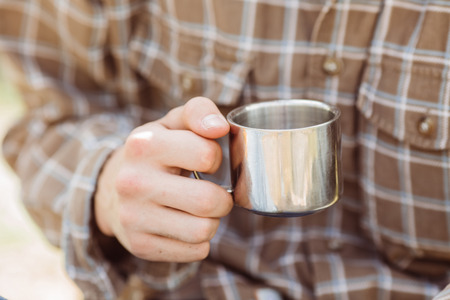 titanium: A person holding a titanium cup of tea while camping