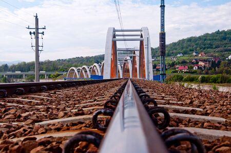 A railway bridge reflecting in a rail.