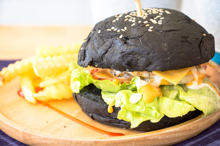 Black Burger with fries and sauce on wooden desk Banque d'images - 95393869