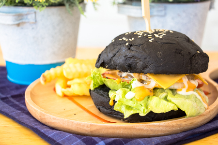 Black Burger with fries and sauce on wooden desk Banque d'images - 95851224