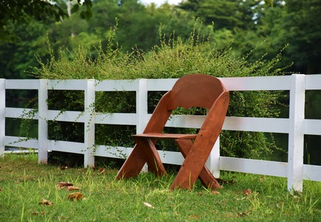 picket green: brown wooden chair in green garden and white picket with nature light,  lonely or waiting concept