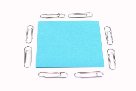 Blank sticky note with paper clip on white background Stock Photo
