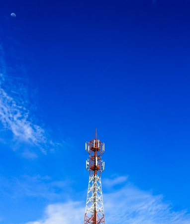 Telecom tower in the afternoon bright sunlight and cloudy blue sky