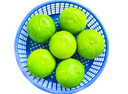 Fresh ripe lime isolated in basket on white