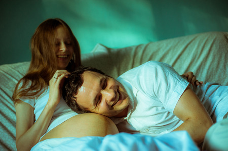 home birth: Image of happy future dad listening the belly of his cheerful caucasian pregnant wife lying on bed at home.