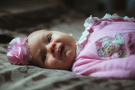 oversleep: Image of cute little girl in pink suit indoor. Newborn baby, caucasian child. Stock Photo