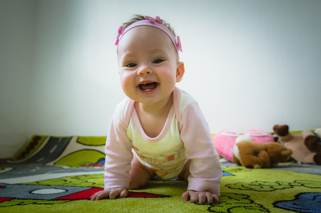 all smiles: Adorable baby girl crawls on all fours on floor at home. Smiling infant of 6 months playing on ground and looking at camera. Portrait of female child. Horizontal shape, front view. Funny kid goes forward.