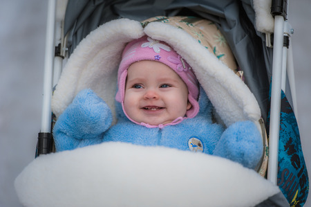 Smiling baby sitting in sledge. Happy infant girl while Hiking in winter. Picture of a newborn in the pink hat and blue overalls, covered with white wool blanket. Red nose.