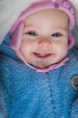 nariz roja: Bebé sonriente sentado en trineo. Feliz niña bebé mientras Senderismo en invierno. Fotografía de un bebé en el sombrero y azules guardapolvos rosados, cubierto con una manta de lana blanca. Nariz roja.