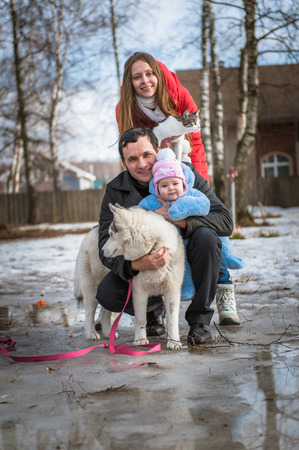 Young lovely family walk in bright sunny winter day. Father, mother, daughter, dog and cat in snowy park. Parent with baby girl and pets. Lifestyle. Woman and man are having walk in countryside. photo