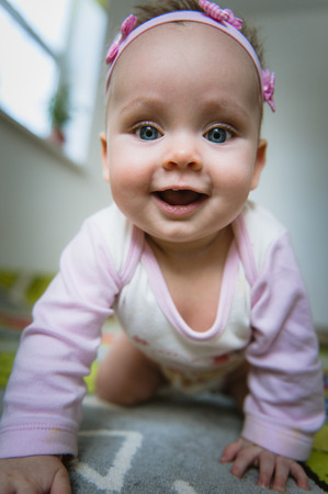 ground floor: Adorable baby girl crawls on all fours on floor at home. Smiling infant of 6 months playing on ground and looking at camera. Portrait of female child. Vertical shape, front view. Funny kid goes forward.