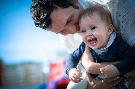 아기: 젊은 아빠의 손에 귀여운 작은 딸의 이미지. 아버지와 아기 소녀 야외. 어린이 놀이터에서 재생됩니다.
