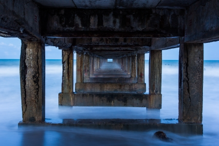 soften: The sea wave is soften and blur under the old bridge for boat fishing