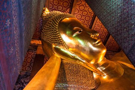 reincarnation: BANGKOK, THAILAND -JAN30, 2011: Reclining Buddha figure in Wat Pho Buddhist temple complex in Bangkok, Thailand.
