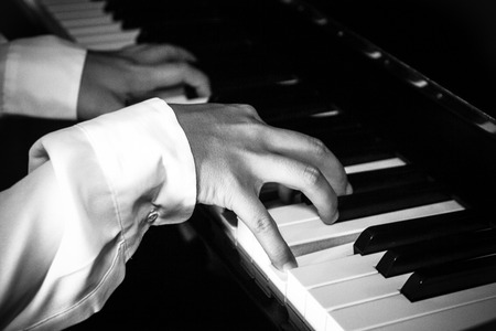 pianista: Hands of female pianist  musician playing piano B&W isolated on black for music concept