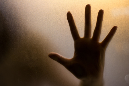 creepy alien: Shadow of hand behind wet glass, close-up Stock Photo