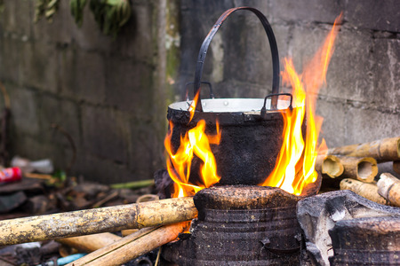 fire bricks: Close up of cooking in cauldron licked by flames on open fire fireplace made of bricks stones in field conditions over blurred nature background, horizontal picture