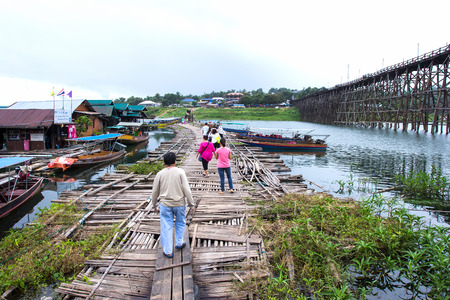 morn: SANGKLABURI, KANJANABURI  - SEP12, 2015: Traveler crossing bamboo bridge or Mon Bridge in Sangklaburi. Kanchanaburi, Thailand. Attractions traditional way of life