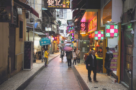 overcrowd: MACAU, CHINA - DEC 9, 2015: Visitors visit the famous souvenir street in Macau. Chinese tourists are the main resource in Macau tourism industry now.