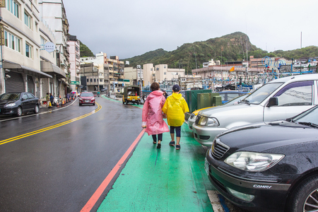 YEHLIU, TAIWAN - OCT11, 2016: Tourists at the Yeliu (Yehliu) Geopark in Wanli District, New Taipei, Taiwan at a rainy, windy and overcast day.