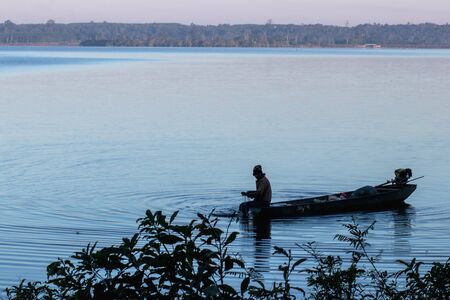 Silhouette of fisherman in blue lake at sunrise time, Thailand.