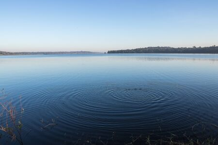 Circles on the blue lake with blue sky.