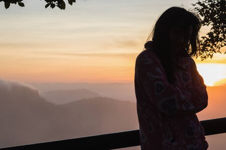 Silhouettes of woman on the mountian at sunrise.