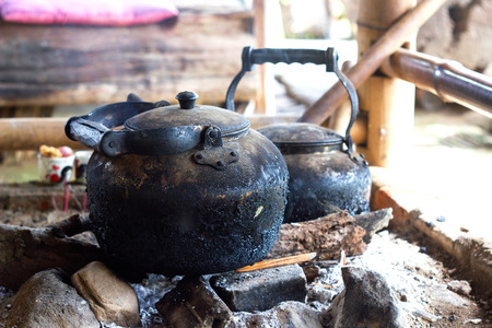 Tea kettle with boiling water on fire wood.