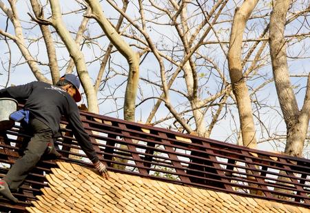 Roofer builder worker dismantling roof shingles.