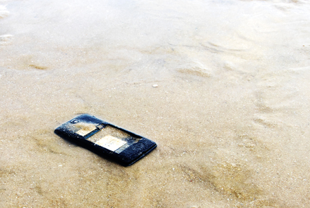 lcd: Close up of broken mobile phone drop on sea beach with copy space, High Contrast, Shallow Depth of Field Stock Photo