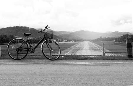 A bicycle stands at near of a runway and mountain