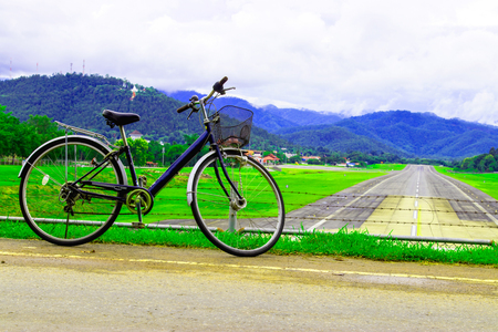 A bicycle stands at near of a runway and mountain with blue sky.