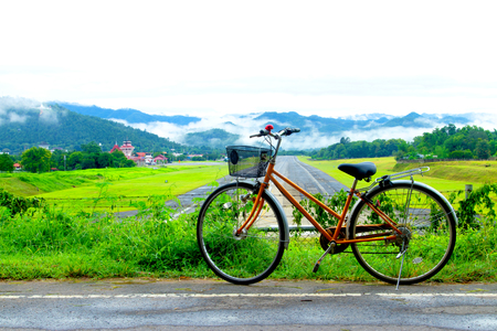 bicycle near Airport runway with mountain in countryside and fog on mountain. Stock Photo