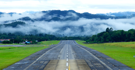 Airport runway with mountain in countryside with fog on mountain. Stock Photo