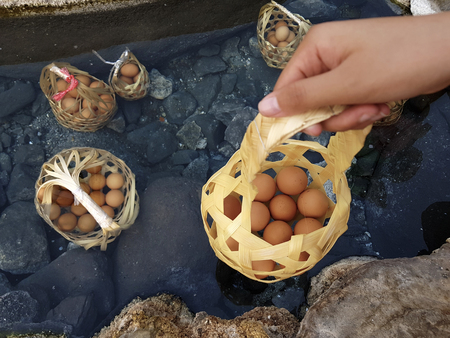 Boiled eggs in natural hot spring, eggs in basket on hand,Soft focus,Select focus. Stock Photo