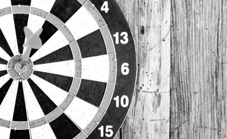Bullseye is a target of business. Dart is an opportunity and Dartboard on old wood background.