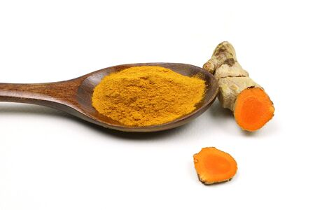 Turmeric powder in a wooden spoon and fresh turmeric roots isolated on a white background is an ingredient in turmeric foods and ingredients in skin care products. Turmeric helps strengthen the skin.