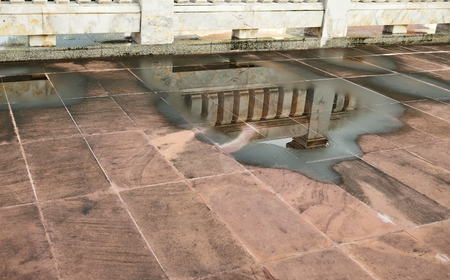 effusion: Capturing the reflection of marble wall and pillar in water logged after rain