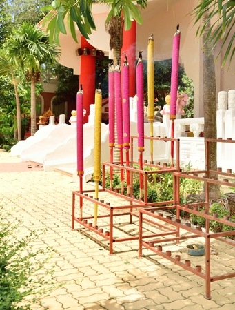 incensed: Many giant colorful joss sticks are incensed in their iron base and another empty base