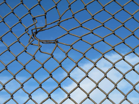 grille: Hole in metallic fence with blue sky background