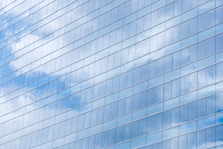 Modern building glass windows with sky reflection.