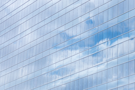 blue clouds: Modern building glass windows with sky reflection.