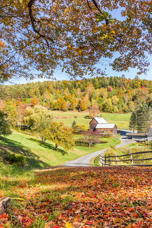 old red barn: Wooden barn in fall foliage landscape in Vermont countryside. Stock Photo