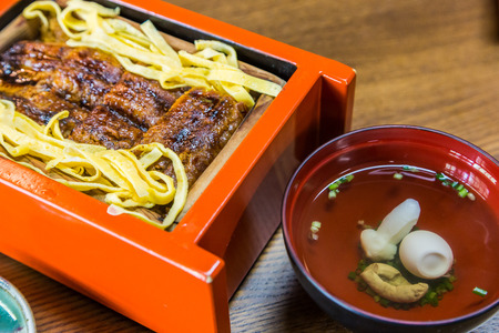 restaurant dining: Unagi don - Grill eel rice in red box with clear soup.