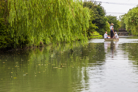 downstream: Yanagawa, JAPAN - AUGUST 18: Tourists cruise on traditional poled boat called Donko which is famous activity in Yanagawa, Fuguoka, Japan on August 18, 2015.