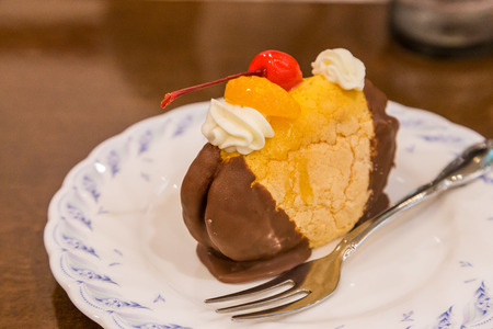 choux bun: Chocolate cream puff with peach and cherry topping
