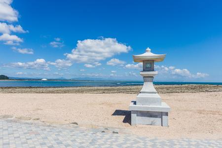 Japanese style stone lamp in white sand beach in Aoshima island, Miyazaki, Japan.