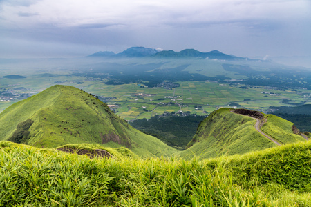 View of Aso volcano mountain and farmer village from hill top in Kumamoto, Kyushu, Japan. Stock Photo