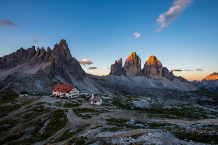 Tre Cime and rifugio hut at sunrise in summer in  Dolomites, Italy