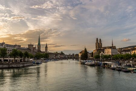 Historic Zurich downtown skyline with Fraumunster and Grossmunster churches at zurich lake during sunset, Switzerland.